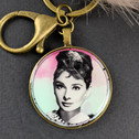 The iconic actress preserved in this 30mm round charm with Pom Pom key ring  is a must have set in vintage bronze with a lobster claw clasp to hang on your purse so you'll never loose your keys.