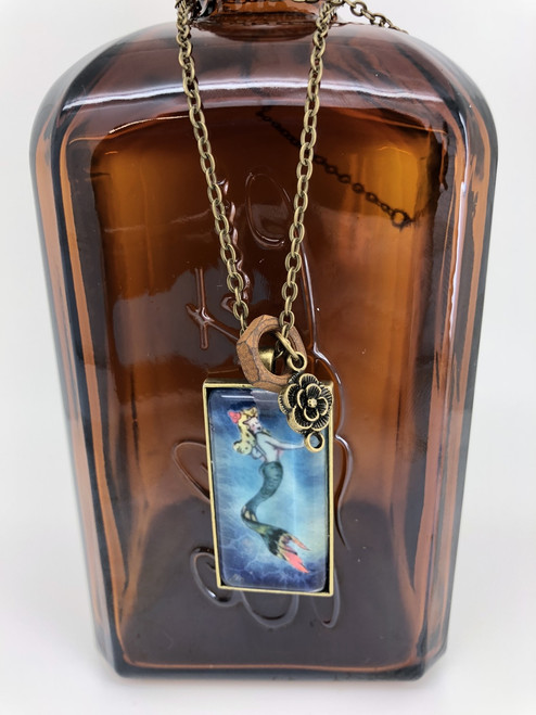 Tipsy Mermaid  1 inch by 2 inch rectangular glass pendant Necklace set in antique brass tray with a 30inch chain with rose and vintage nut charm.