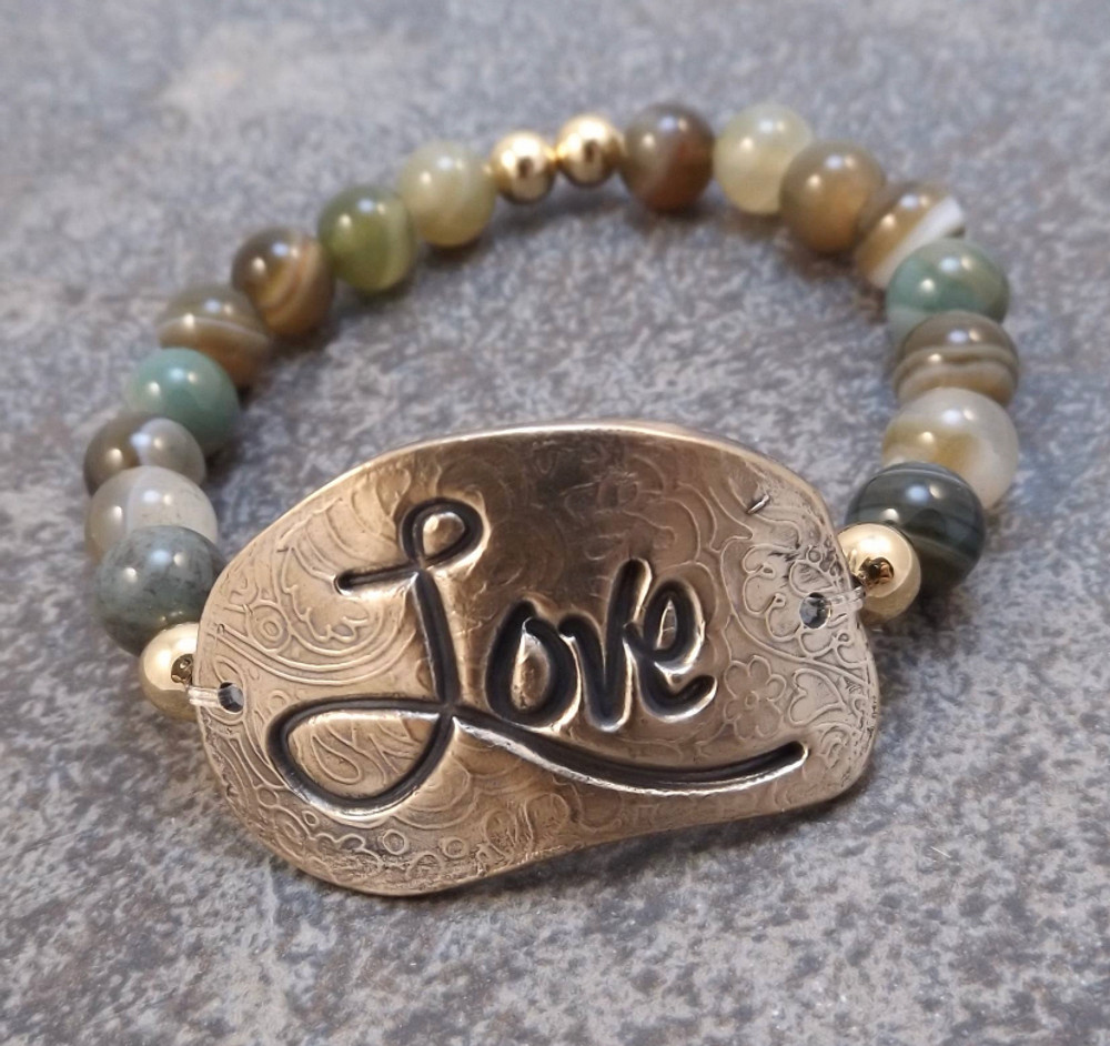 """This handmade Bronze stretch bracelet is a member of the updated """"inspiration"""" bracelet series. The focal of each piece is a hand formed solid bronze bracelet plate (1-5/8 x 3/4"""")  The surrounding beads are 8mm smooth Green Brown Agate.  This bracelet is stretchable and should therefore fit most wrists."""