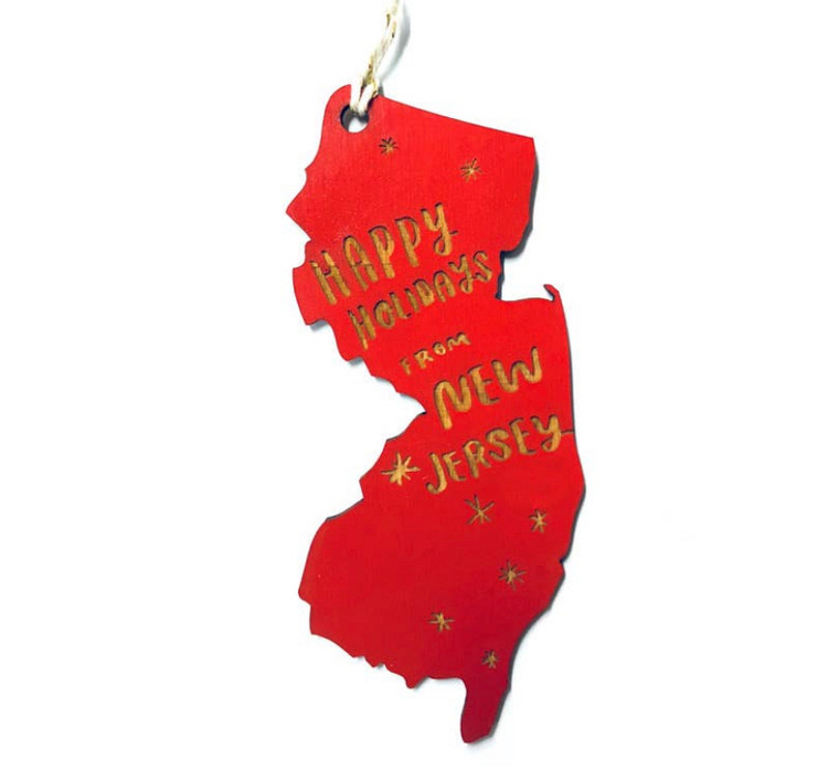 """Spread the New Jersey love far and wide with a handcrafted ornament!  Laser-cut wooden ornament in the shape of New Jersey engraved with the words 'Happy Holidays From New Jersey'     *Hand strung with gold and white baker's twine   *Ornament measures approximately 5"""" x 2.5"""""""