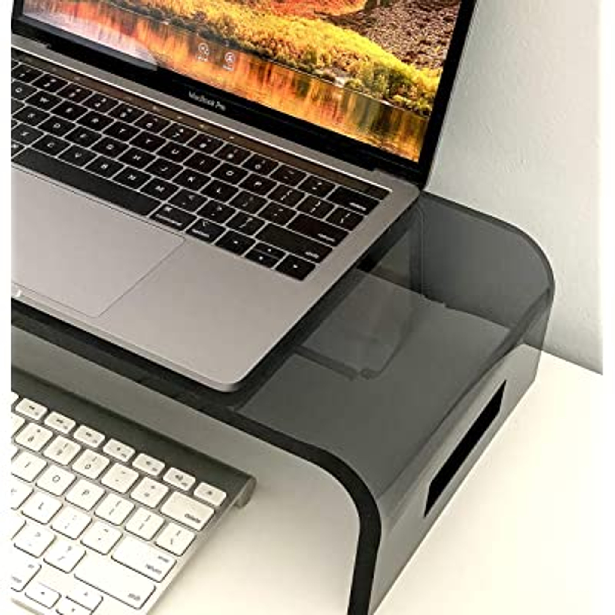 A Smoke Grey Acrylic Computer Riser is designed to raise your monitor height and store your keyboard underneath.