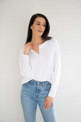 A casual basic; this henley snap top is simple to care for, pair and wear dressed up or down. The front hem carries from the waist up to the shoulder, creating a raw line detail. Add this to your collection of quick go-to basics tees.