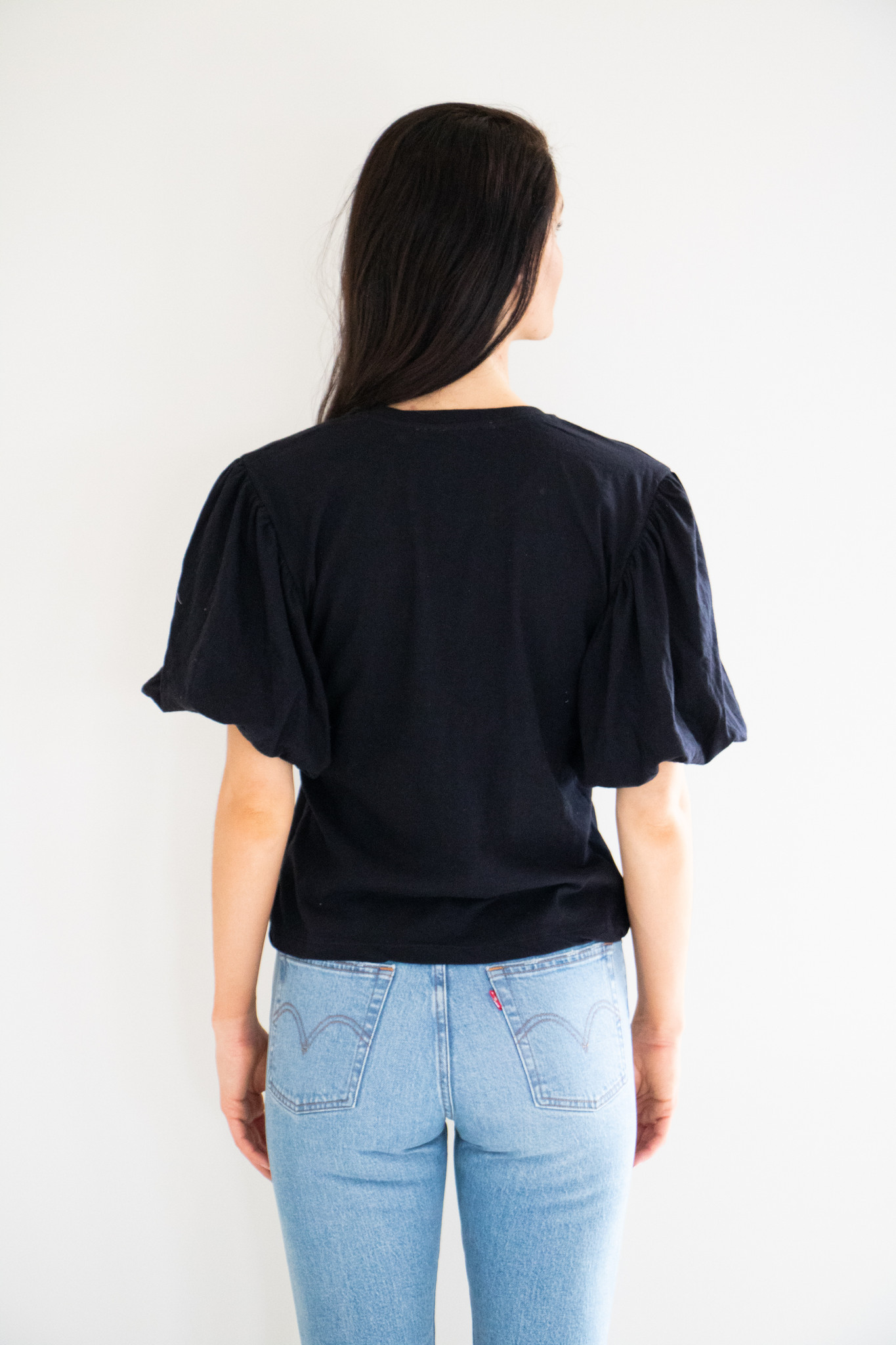 Peplum sleeve details add a feminine edge to this basic tee. Slightly boxy though the body with a finished crew neck, easily parable and comes in classic black and white.