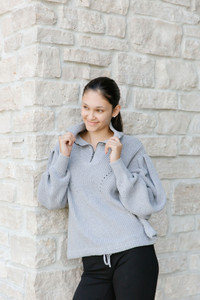 This stunning half zip sweater features a soft drop shoulder for a trendy, bell sleeve look.  With a tie at the waist, you can wear this long or cinch it for more of a cropped look.  Pair with jeans, for an easy look.
