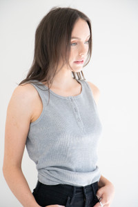 A casual basic waffle knit tank, featuring a henley button down neckline, ribbed arm and neck openings and made from a light weight cotton fabric.