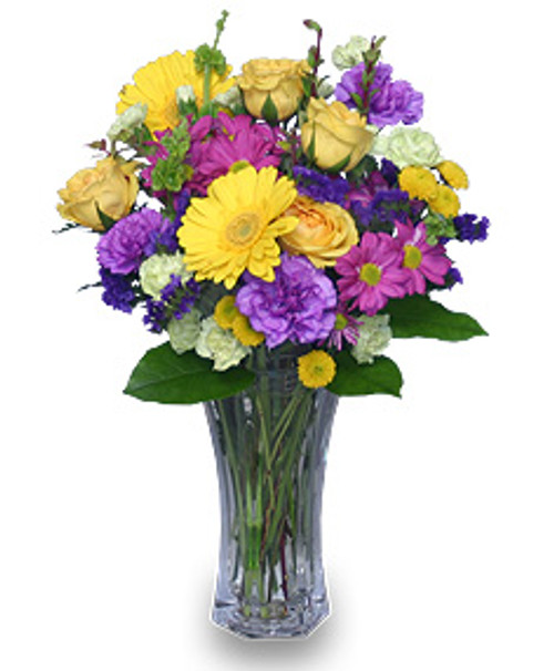"""8 1/2"""" flared rose vase foliage: salal, leather leaf 4 yellow roses 2 yellow gerberas 2 stems fuchsia daisy poms 3 stems purple 'Sinuata' statice 3 stems apple-green mini carnations 4 purple 'Moonshade' carnations 2 stems yellow button poms"""