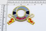 """Marine Life Preserver with Flags Iron On Applique  Embroidered on Twill Backing with Rayon and Metallic Threads  Measures 2 1/4"""" high x 3 1/2"""" wide approximately"""