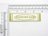 "Chewing Gum Gold Iron On Patch Applique  Fully Embroidered with Rayon and Metallic Threads  Measures 1"" high x 3 3/4"" wide approximately"