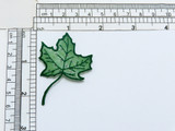 """Maple Leaf Sheer Glitter Dot Green Iron On Applique  Embroidered Border and vein detail on a sheer backing with multi glitter dot details  Measures 2 3/8"""" long x 1 5/8"""" wide"""