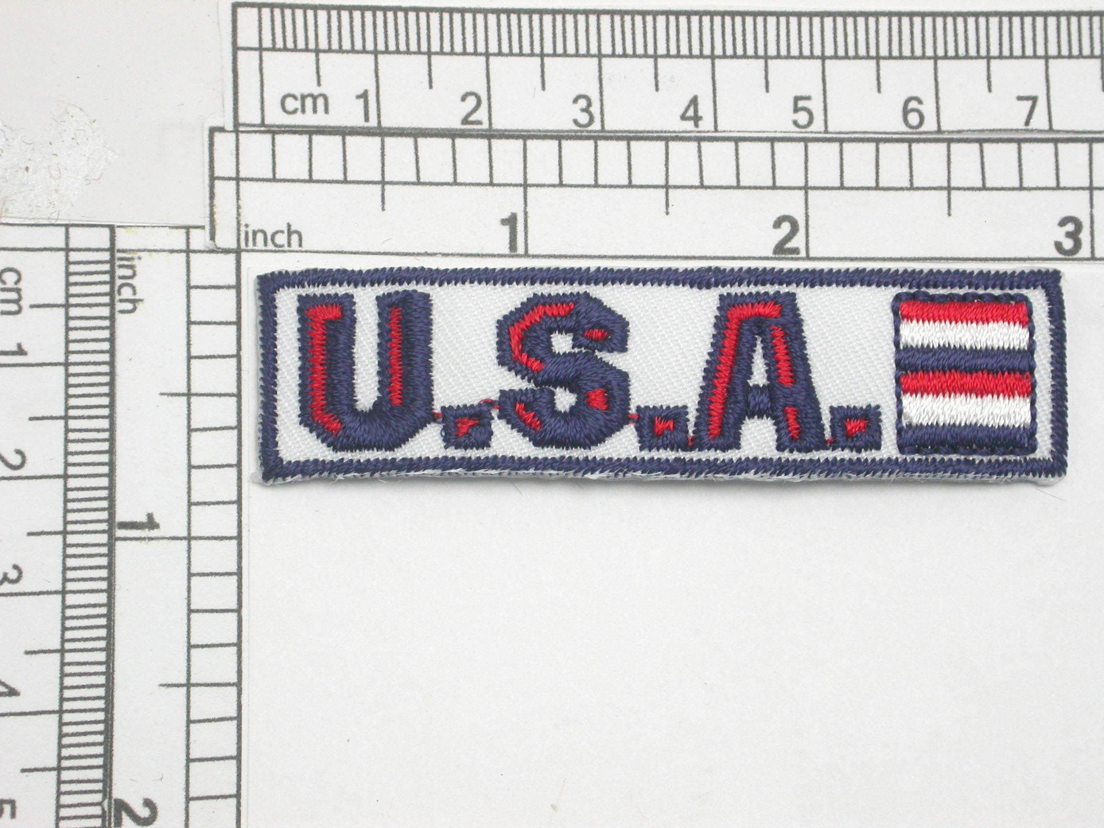 """USA Patriotic Iron On Patch Applique    Embroidered with rayon  Thread on a White Twill Backing   Measures 2 3/42"""" across by 3/4"""" high"""