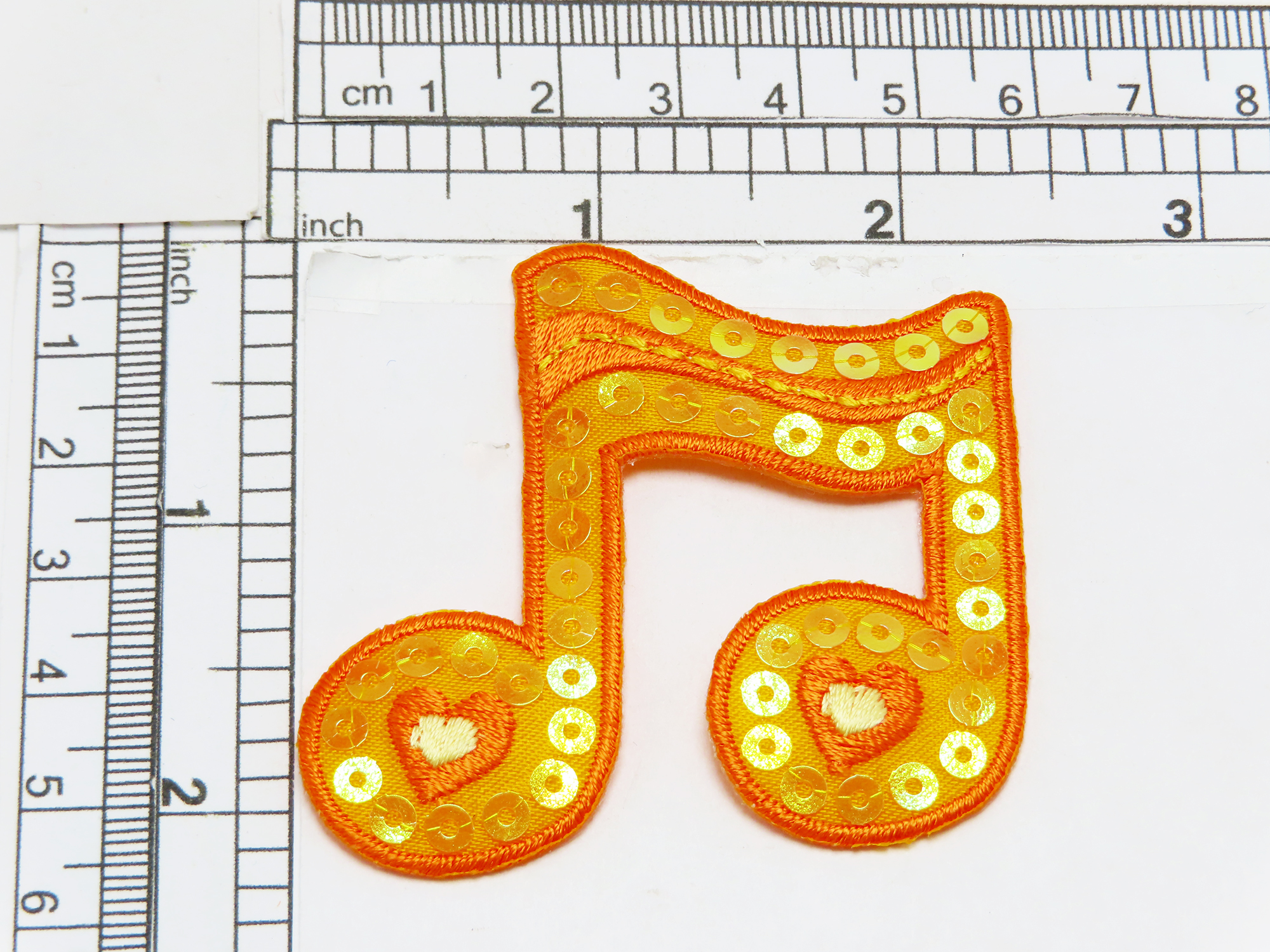 """Music Note Patch Sequin Orange  Embroidered on  Orange Sateen Backing and decorated with sewn on sequins Measures  2 3/8"""" across x 2 1/4"""""""