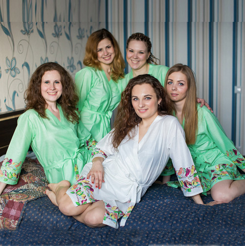 Bridesmaids and the bride in mint and white bird themed getting ready robes