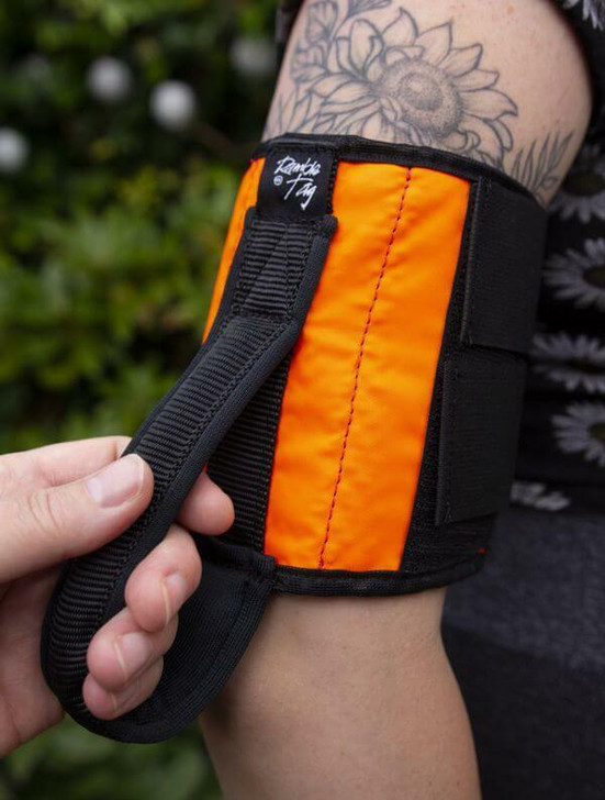 An Orange Ramble Tag Original Mobility Guidance Aid on a persons arm while providing enhanced guidance for individuals with sight loss.