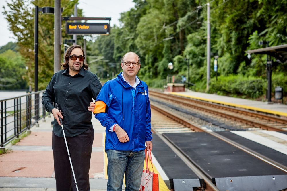 Image of B. Fox holding onto Bari Azman with a Ramble Tag mobility guidance aid while standing on a light rail platform