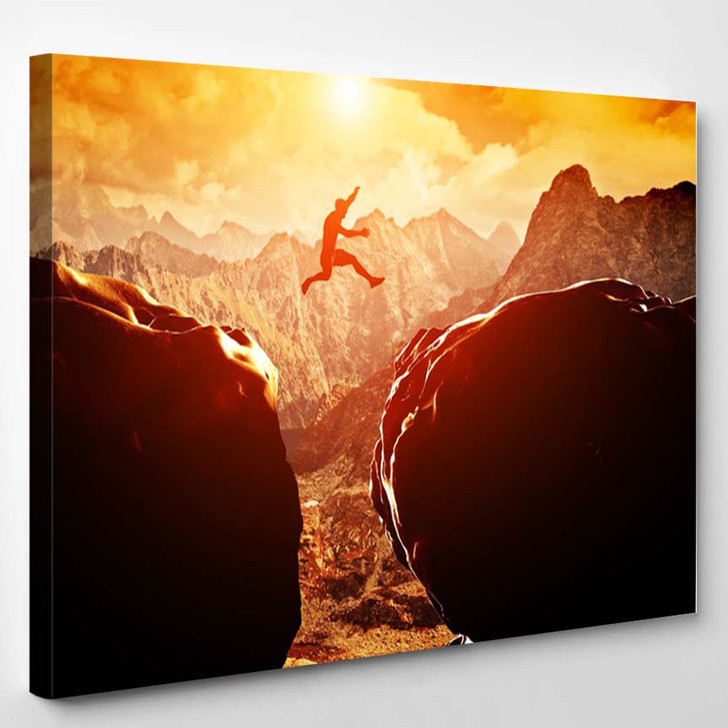 Man Jumping Over Precipice Between Two Rocky Mountains - Sports And Recreation Canvas Art Print