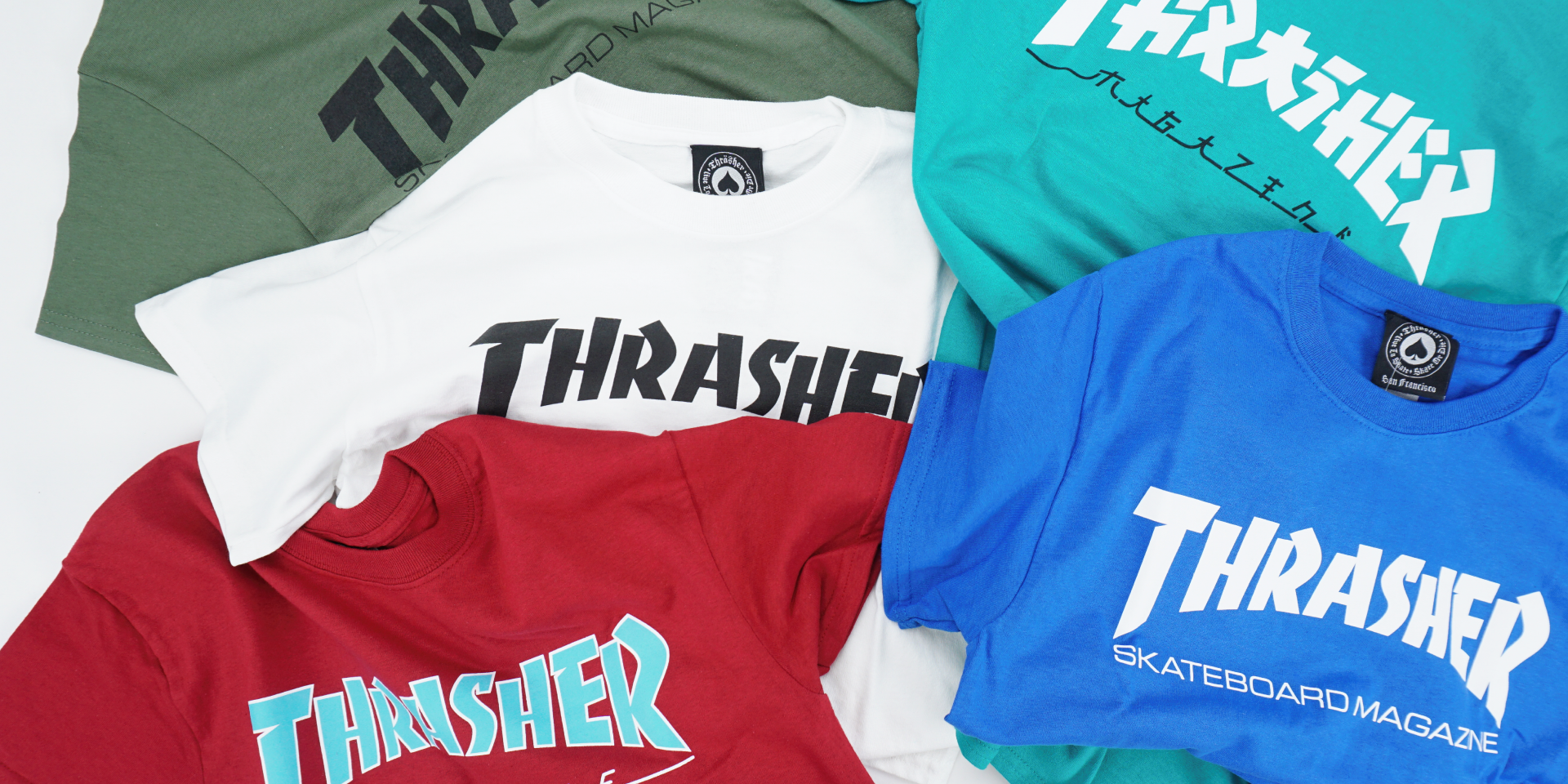 Stack of thrasher T-Shirts in Green, Blue, Red and white, with classic thrasher logo