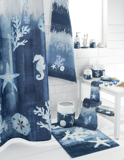 Avanti Home Batik Coastal Collection style shot containing countertop bath accessories, towels, shower curtain, shower hooks and rug, arranged stylishly to showcase the blue and white Ombre design.