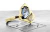 SANTORINI .50 carat icy white diamond 1.28 carat blue sapphire 14k yellow gold 2mm flat band 3/4 view on metal background with Chinchar/Maloney logo
