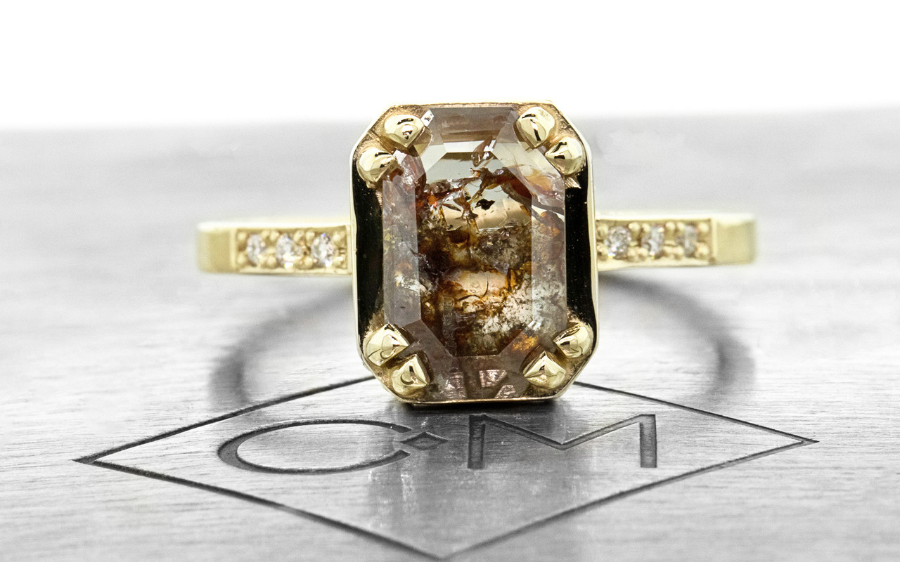 MAROA 1.07 carat  fancy-cut translucent rustic cognac diamond ring set in our signature square setting, set in 14k yellow gold. With ten 1.2mm brilliant white diamonds set into notched band and in each corner of main setting. Part of our New Classic Collection. Front view on metal background with Chinchar/Maloney logo