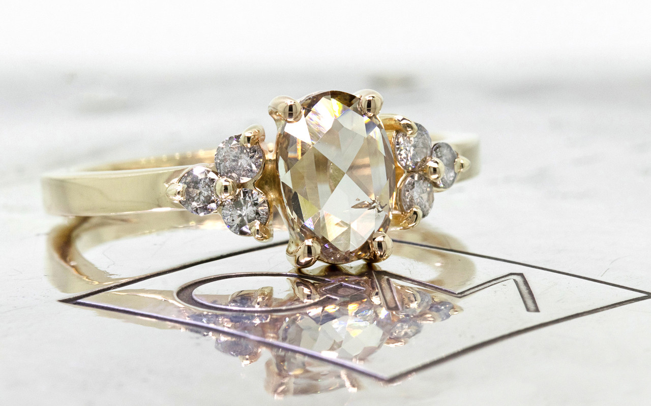 .79 carat oval, rose-cut prong set champagne diamond ring with six 2mm brilliant gray diamond clusters on either side of main setting set in 14k yellow gold flat band. 3/4 view on metal background with Chinchar/Maloney logo