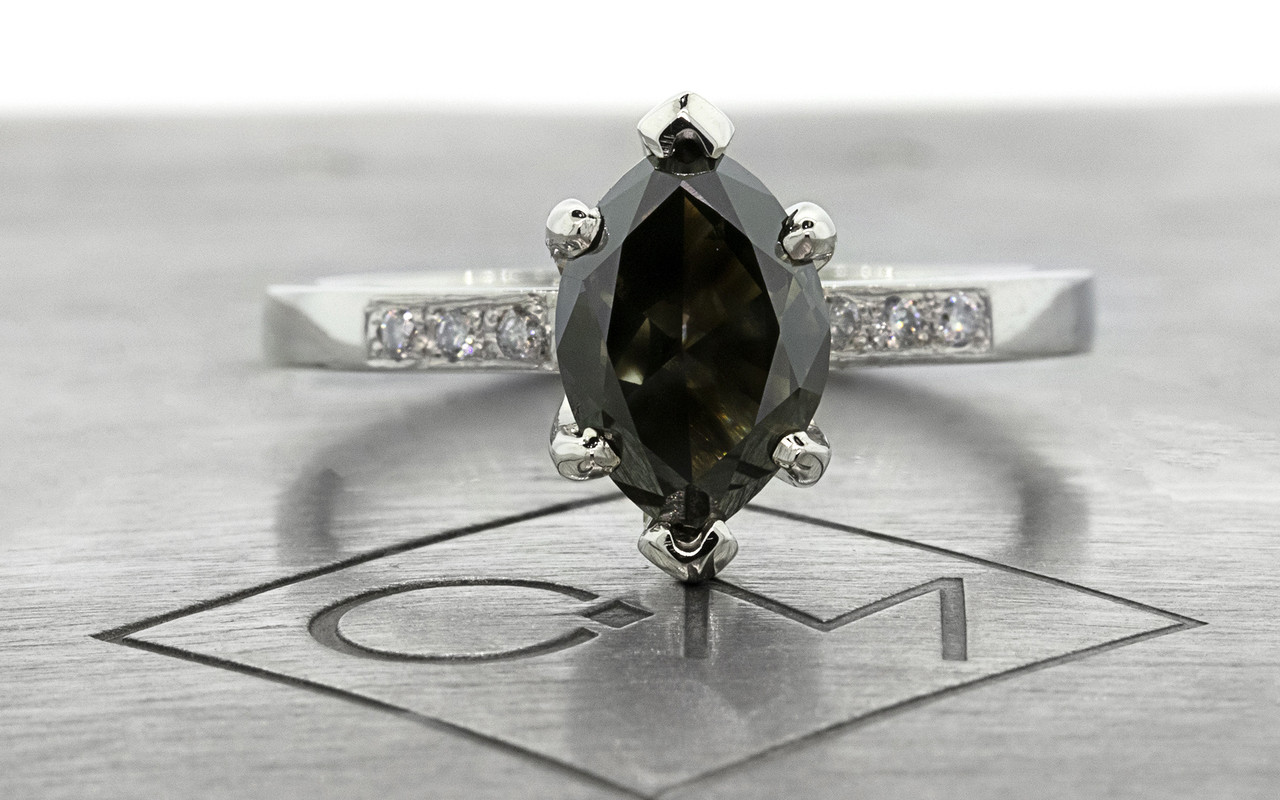 One of a kind, this natural, translucent, black diamond weighs 1.53 carats. marquise, faceted cut prong set diamond. Set into 14k recycled white gold 2mm flat band with six 1.2mm brilliant gray diamonds bead set into band. Front view on metal background with Chinchar/Maloney logo