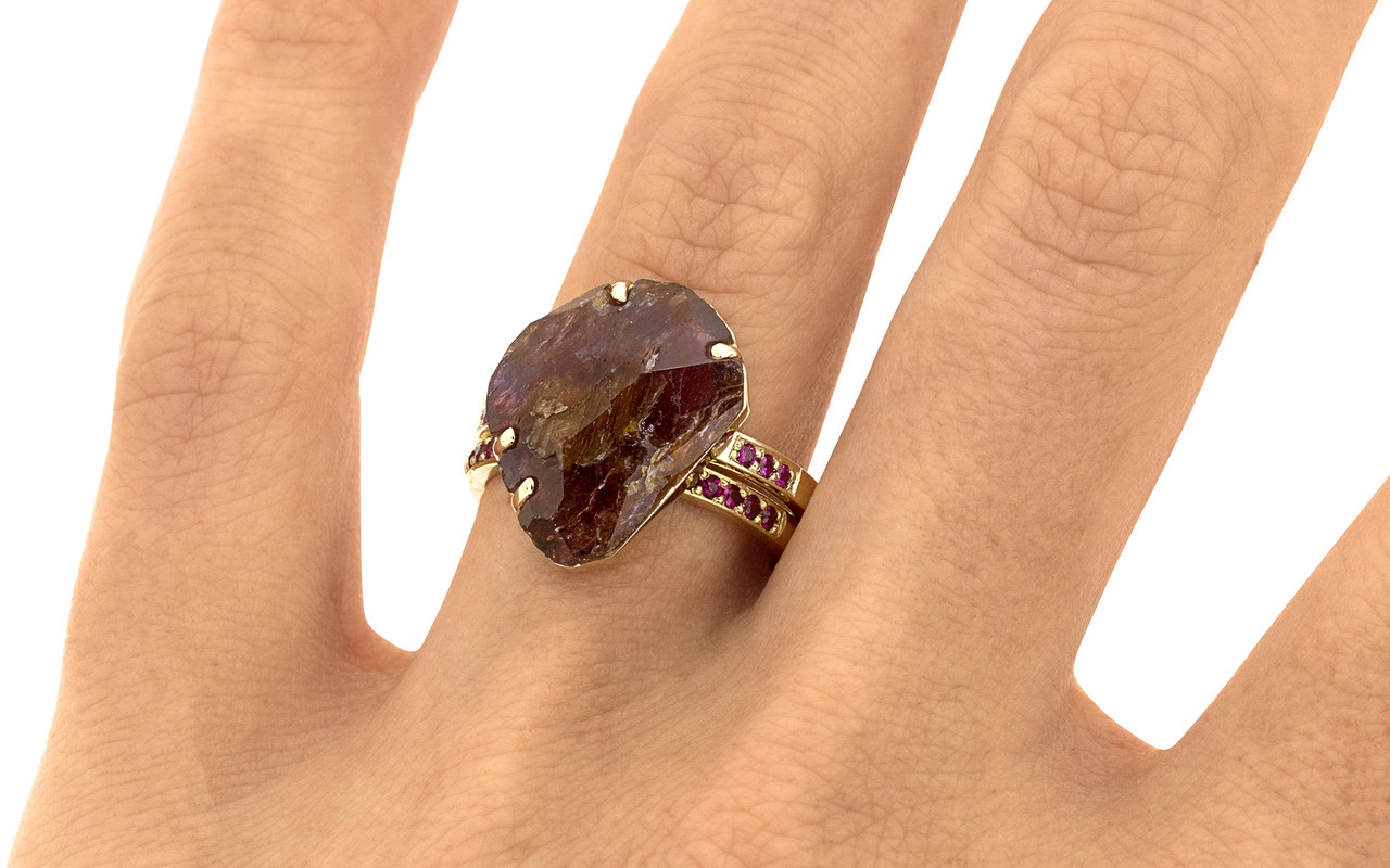 a one-of-a-kind, partially hand-cut and polished, 5.88 carat ruby. The prongs in our original design have been inlaid into grooves carved into the gem for a secure and smooth setting. Six brilliant rubies have been bead-set into the 14k recycled yellow gold 2mm flat band. Part of our Refined Rough Collection. With Wedding Band with 16 Rubies. 16 vibrant rubies pave set into a 14k recycled gold 2mm 1/2 round band on a hand