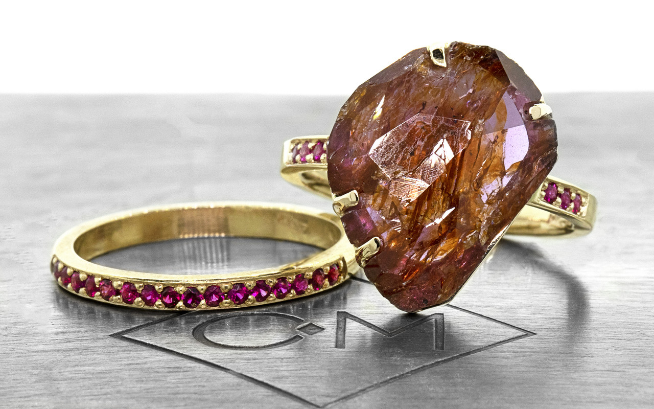 a one-of-a-kind, partially hand-cut and polished, 5.88 carat ruby. The prongs in our original design have been inlaid into grooves carved into the gem for a secure and smooth setting. Six brilliant rubies have been bead-set into the 14k recycled yellow gold 2mm flat band. Part of our Refined Rough Collection. With Wedding Band with 16 Rubies. 16 vibrant rubies pave set into a 14k recycled gold 2mm 1/2 round band. Front view on metal background with Chinchar/Maloney logo.