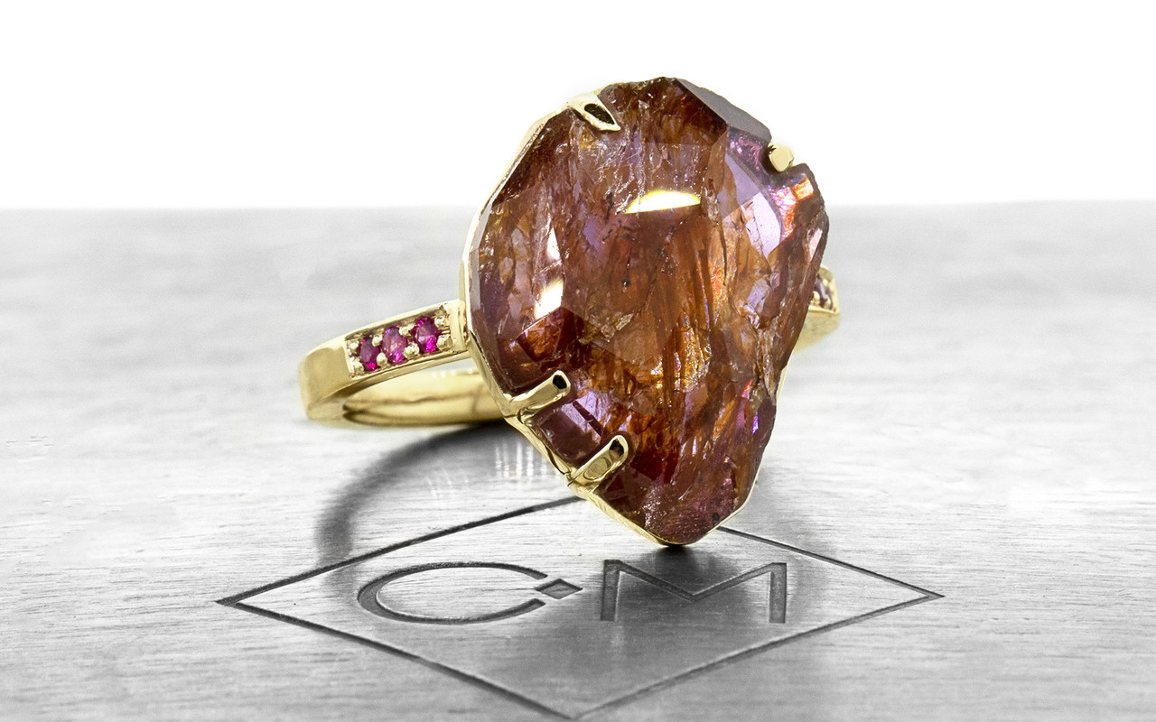 a one-of-a-kind, partially hand-cut and polished, 5.88 carat ruby. The prongs in our original design have been inlaid into grooves carved into the gem for a secure and smooth setting. Six brilliant rubies have been bead-set into the 14k recycled yellow gold 2mm flat band. Part of our Refined Rough Collection. 3/4 view on metal background with Chinchar/Maloney logo