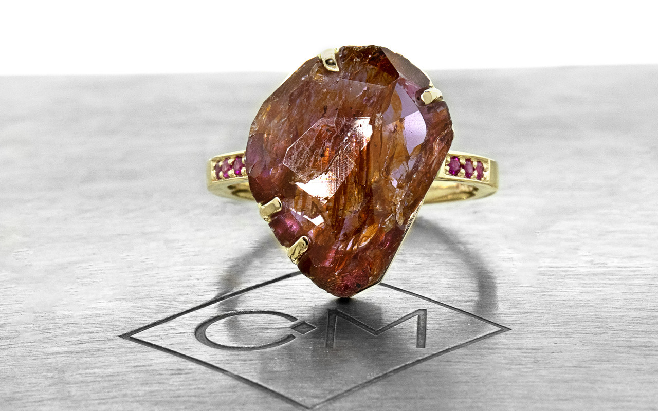 a one-of-a-kind, partially hand-cut and polished, 5.88 carat ruby. The prongs in our original design have been inlaid into grooves carved into the gem for a secure and smooth setting. Six brilliant rubies have been bead-set into the 14k recycled yellow gold 2mm flat band. Part of our Refined Rough Collection. Front view on metal background with Chinchar/MAloney logo.