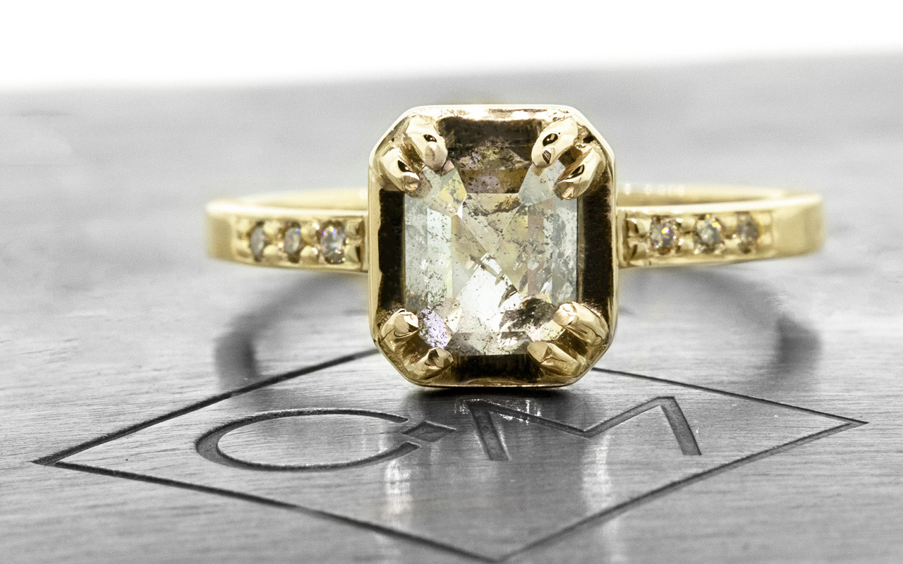 """MAROA one-of-a-kind, fancy-cut, 1.41 carat """"salt and pepper"""" diamond set in our New Classic setting. 1.2mm, brilliant champagne diamonds set into the 14k recycled yellow gold 2mm notched band. Part of our New Classic Collection. Front view on metal background with Chinchar/Maloney logo"""