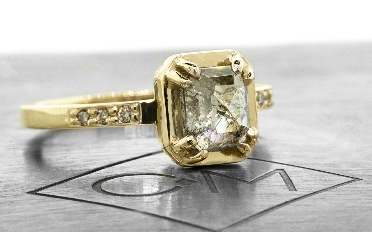 """MAROA one-of-a-kind, fancy-cut, 1.41 carat """"salt and pepper"""" diamond set in our New Classic setting. 1.2mm, brilliant champagne diamonds set into the 14k recycled yellow gold 2mm notched band. Part of our New Classic Collection. 3/4 view on metal background with Chinchar/Maloney logo"""