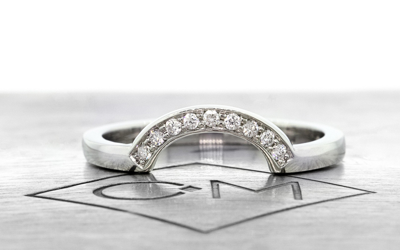 Our Curved Shadow Band features 10 brilliant white diamonds.  We can customize this ring with champagne or gray diamonds as well. band fits beautifully with many of our engagement rings and can also be customized. 14k recycled white gold this ring can also be made in 14k recycled yellow or rose gold. Front view on metal background with Chinchar/Maoney logo