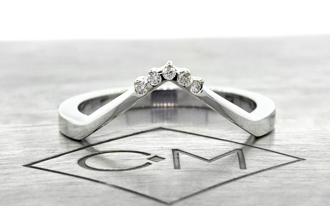 V Shadow Band features 5 brilliant white diamonds.  We can customize this ring with champagne or gray diamonds as well. 14k recycled white gold this ring can also be made in 14k recycled yellow or rose gold. Can also be customized to fit a specific setting. Front view on metal background with Chinchar/Maloney logo