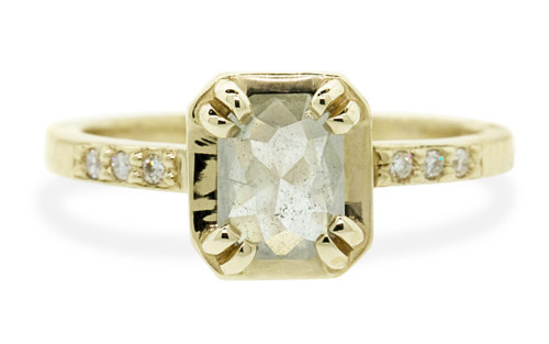MAROA .74 carat oval, rose-cut, glowing icy white diamond ring set in our signature square setting, set in 14k yellow gold. With ten 1.2mm brilliant white diamonds set in notched band and each corner of main setting. Part of our New Classic Collection. Front view on white background