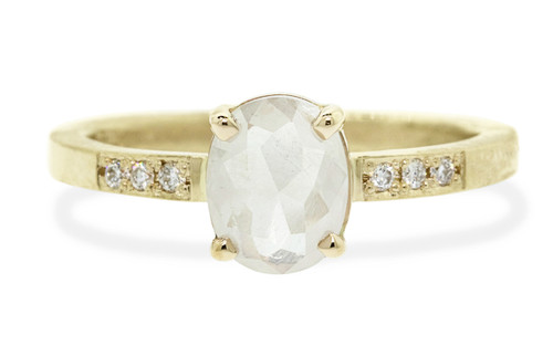 .80 carat oval, rose cut opalescent rustic white prong set diamond ring with six 1.2mm brilliant white diamonds set into band set in 14k yellow gold flat band. Front view on white background