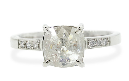 1.68 carat cushion, faceted cut rustic icy white prong set diamond ring set in 14k white gold with six 1.2mm brilliant white diamonds set in flat band. Front view on white background