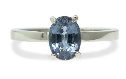 1.59 carat oval rose cut blue sapphire set in 14k white gold flat band. Front view on white background