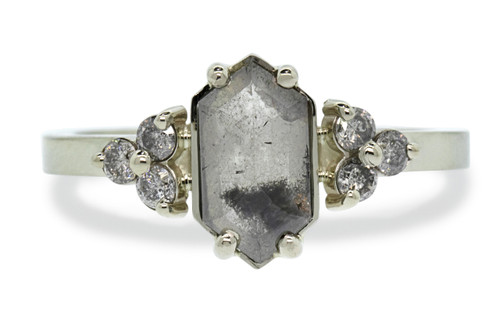 1.10 carat fancy, rose-cut semi-translucent gray color with an inky, black splash prong set diamond ring. With six 2mm brilliant gray diamond clusters on either side of main diamond setting and 14k recycled white 2mm flat gold band. Front view on white background