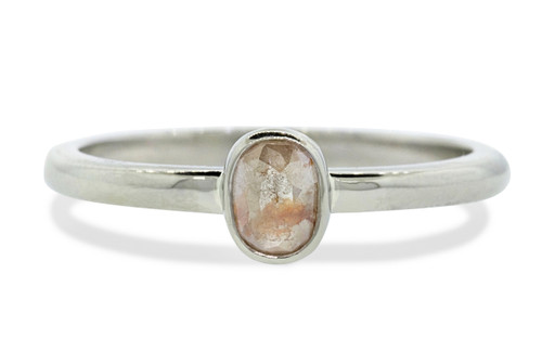 .43ct diamond has gorgeous, light peach color. oval, rose cut diamond. diamond measures 5.5mm x 4.5mm. The ring is entirely 14k recycled white gold. Front  view on white background