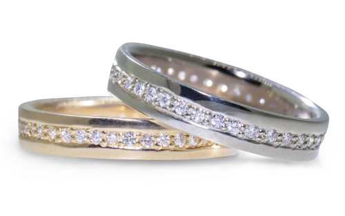 Wedding bands in 14k yellow gold and 14k white gold with white diamonds bead pave set down the center in eternity style.  On white background.