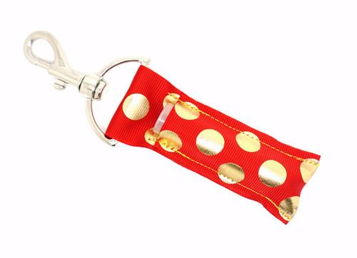 Lip Balm Holder Red with Gold Foil Dots   Each Lip Balm / Chapstick Holder is HANDMADE with a high-quality material! Our unique design's and clasp offer both style and functionality. The hook is also on a swivel head so the lip balm always falls back down and never gets stuck upside down, this is where most lip balm holders lose your lip balm or chapstick! The holder is designed to snuggly fit nice and cozy any standard chapstick or lip balm. This ensures that the lip balm / chapstick won't fall out when needed most.   BENEFITS: Misplacing or Losing your chapstick is the worst!! Don't let that happen again and buy the perfect solution! Our Lip Balm / Chapstick Holder Keychain will make sure you always have your Gettin Lippy lip balm at hand when desperately needed. Our cute fun designs will compliment anything. Attach it to your keys, lanyard, back-pack, bag, purse, or anywhere your little heart desires with our easy open clasp!   PERFECT GIFTS: A simple gift can go a long way. Everyone needs something cute and functional. Buy now for stocking stuffers, birthday party, a team gift or for a daughter, friend, wife, girlfriend, colleague, student, teacher, etc!  BUY WITH CONFIDENCE: Read the reviews! Our Gettin Lippy Lip balm holders are the number one rated lip balm holder on the market! If you don't LOVE our product, we offer 100% Money Back GUARANTEE no questions asked.   PACKAGE INCLUDES:  1 Unique Lip Balm / Chapstick holder. Each Holder is 6.5 inches (with hook) x 1.5 inches. **NOTE: Gettin Lippy lip balms in pictures are not included but click on the link below and get the best multi-flavored lip balm on the market:   https://gettinlippy.com/gettin-lippyoriginal-line/     MADE IN THE USA!!