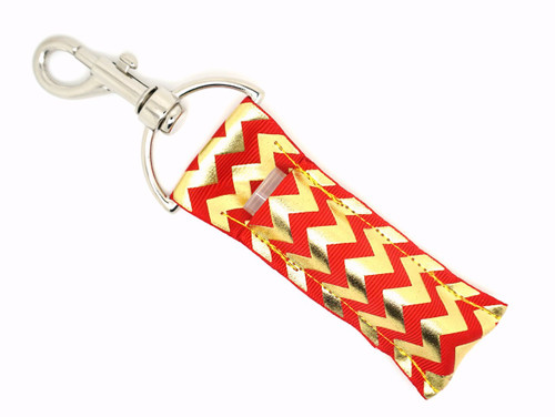Lip balm holder Red and Gold Foil Chevron    Each Lip Balm / Chapstick Holder is HANDMADE with a high-quality material! Our unique design's and clasp offer both style and functionality. The hook is also on a swivel head so the lip balm always falls back down and never gets stuck upside down, this is where most lip balm holders lose your lip balm or chapstick! The holder is designed to snuggly fit nice and cozy any standard chapstick or lip balm. This ensures that the lip balm / chapstick won't fall out when needed most.   BENEFITS: Misplacing or Losing your chapstick is the worst!! Don't let that happen again and buy the perfect solution! Our Lip Balm / Chapstick Holder Keychain will make sure you always have your Gettin Lippy lip balm at hand when desperately needed. Our cute fun designs will compliment anything. Attach it to your keys, lanyard, back-pack, bag, purse, or anywhere your little heart desires with our easy open clasp!   PERFECT GIFTS: A simple gift can go a long way. Everyone needs something cute and functional. Buy now for stocking stuffers, birthday party, a team gift or for a daughter, friend, wife, girlfriend, colleague, student, teacher, etc!     BUY WITH CONFIDENCE: Read the reviews! Our Gettin Lippy Lip balm holders are the number one rated lip balm holder on the market! If you don't LOVE our product, we offer 100% Money Back GUARANTEE no questions asked.   PACKAGE INCLUDES:  1 Unique Lip Balm / Chapstick holder. Each Holder is 6.5 inches (with hook) x 1.5 inches. **NOTE: Gettin Lippy lip balms in pictures are not included but click on the link below and get the best multi-flavored lip balm on the market:   https://gettinlippy.com/gettin-lippyoriginal-line/     MADE IN THE USA!!