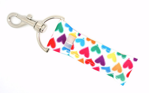 Hearts Lip balm Holder  This lip balms holder is very durable with a stainless steel hook that is easily attached and unattached to a purse, keys, backpack, or lanyard. This lip balm holder is white background with multi-colored hearts.  MADE IN THE USA!!