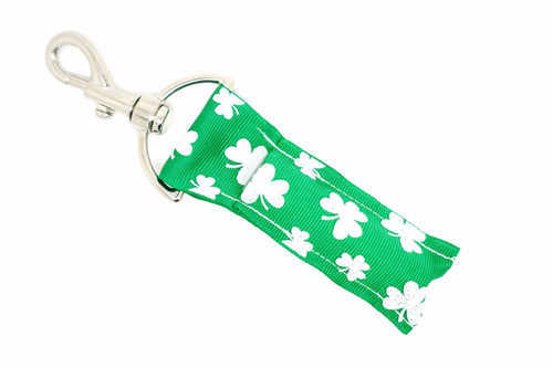 Green with white glitter shamrocks lip balm holder  This lip balms holder is very durable with a stainless steel hook that is easily attached and unattached to a purse, keys, backpack, or lanyard. This lip balm holder is green with white shamrocks with glitter.  MADE IN THE USA!!