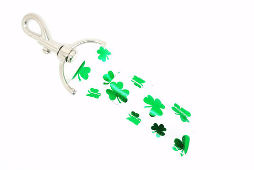 White with green foil shamrocks lip balm holder  Each Lip Balm / Chapstick Holder is HANDMADE with a high-quality material! Our unique design's and clasp offer both style and functionality. The hook is also on a swivel head so the lip balm always falls back down and never gets stuck upside down, this is where most lip balm holders lose your lip balm or chapstick! The holder is designed to snuggly fit any standard chapstick or lip balm. This ensures that the lip balm / chapstick won't fall out when needed most.   BENEFITS: Misplacing or Losing your lip balm or chapstick is the worst!! Don't let that happen again and buy the perfect solution! Our Lip Balm / Chapstick Holder Keychain will make sure you always have your Gettin Lippy lip balm at hand when desperately needed. Our cute fun designs will compliment anything. Attach it to your keys, lanyard, back-pack, bag, purse, or anywhere your little heart desires with our easy open clasp!   PERFECT GIFTS: A simple gift can go a long way. Everyone needs something cute and functional. Buy now for stocking stuffers, birthday party, a team gift or for a daughter, friend, wife, girlfriend, colleague, student, teacher, etc!   BUY WITH CONFIDENCE: Read the reviews! Our Gettin Lippy Lip balm holders are the number one rated lip balm holders on the market! If you don't LOVE our product, we offer 100% Money Back GUARANTEE no questions asked.   PACKAGE INCLUDES:  1 Unique Lip Balm / Chapstick holder. Each Holder is 6.5 inches (with hook) x 1.5 inches. **NOTE: Gettin Lippy lip balms in pictures are not included but click on the link below and get the best multi-flavored lip balm on the market: https://gettinlippy.com/holiday-lip-balms/st-patricks-day-lip-balms/     HANDMADE IN THE USA!!