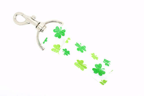 White lip balm holder with light and dark green shamrocks with glitter  This lip balms holder is very durable with a stainless steel hook that is easily attached and unattached to a purse, keys, backpack, or lanyard. This lip balm holder is white with light green and dark green shamrocks with glitter.  MADE IN THE USA!!