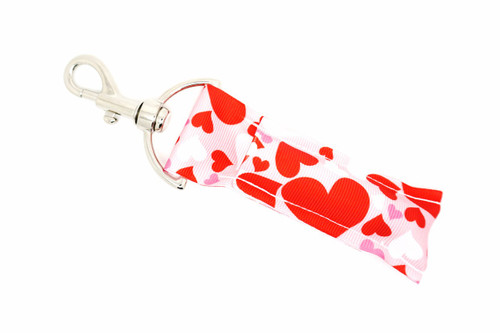 Hearts Lip balm Holder pink with red white and pink hearts  This lip balms holder is very durable with a stainless steel hook that is easily attached and unattached to a purse, keys, backpack, or lanyard. This lip balm holder has a pink background with red white and pink hearts.  MADE IN THE USA!!