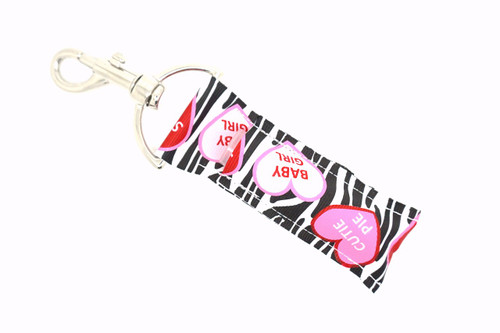 Zebra Lip balm Holder with Valentine's Day hearts  This lip balms holder is very durable with a stainless steel hook that is easily attached and unattached to a purse, keys, backpack, or lanyard. This lip balm holder has a zebra background with Valentine's Day hearts that say cutie pie, baby girl, swak, Luv YA, Be Mine, Kiss!  MADE IN THE USA!!