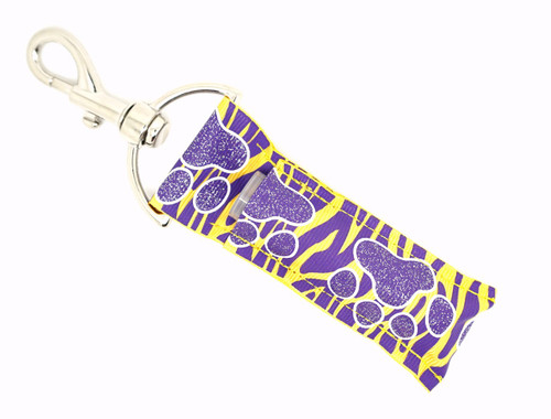 Purple and glitter Paw prints on top of purple and yellow zebra print Lip Balm Holder   This lip balms holder is very durable with a stainless steel hook that is easily attached and unattached to a purse, keys, backpack, or lanyard. This lip balm holder has a purple with glitter paw prints on top of purple and yellow zebra print!  MADE IN THE USA!!