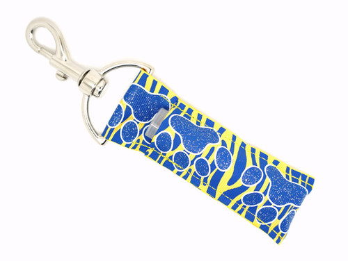 Blue and glitter Paw prints on top of blue and yellow zebra print Lip Balm Holder   This lip balms holder is very durable with a stainless steel hook that is easily attached and unattached to a purse, keys, backpack, or lanyard. This lip balm holder has a blue with glitter paw prints on top of blue and yellow zebra print!  MADE IN THE USA!!